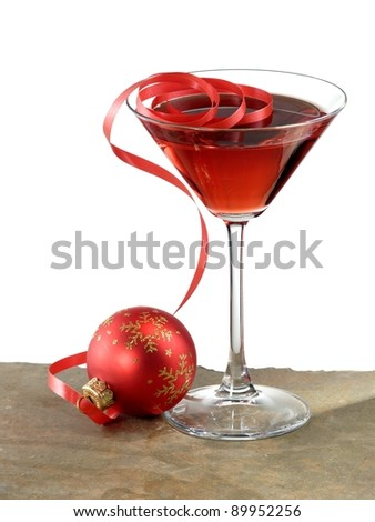 Red cocktail in martini glass with red christmas ball for Christmas in a glass cocktail
