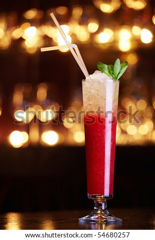 Red cocktail in the extended glass with straws