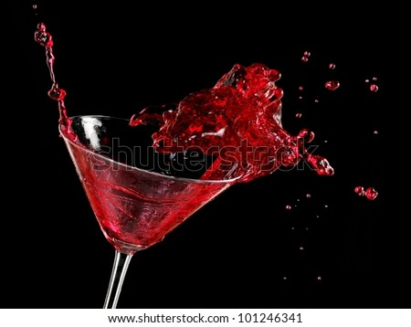 Red cocktail splash in a martini glass