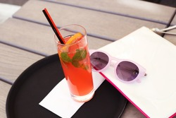 Red cocktail with ice and mint on a tray. Cocktail and sunglasses. Alcoholic cocktail on the table in the lounge area. Lounge cafe. Tinted photo. Tray, cloth,  sunglasses and bag.  Selective focus.