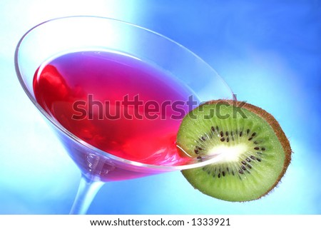 Red cocktail with kiwi garnish and blue light background