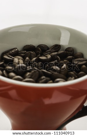 Red coffee cup full of beans