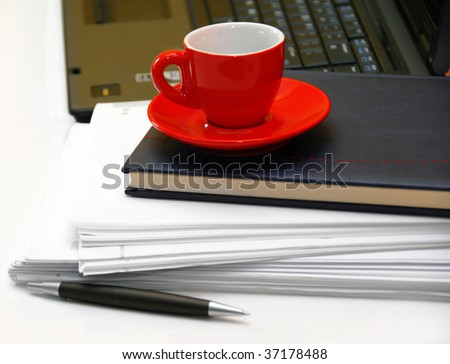 red coffee cup over black notebook on office desk