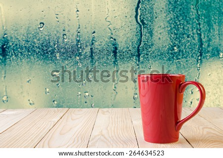 red coffee cup with natural water drops on glass window background