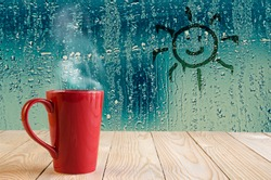 red coffee cup with smoke and sun sign on water drops glass window background