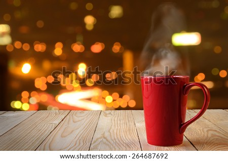 red coffee cup with smoke on city bokeh background