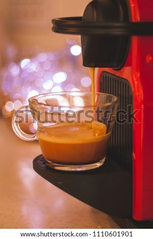 Red coffee machine pours fresh hot coffee into a clear glass Espresso cup. soft out of focus lighting in background. Warm brown tones. Crema on coffee. #1110601901