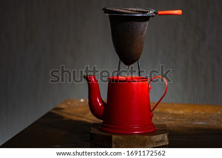 red coffee maker and cloth filter, with dark background. red teapot. coffee. rustic coffee