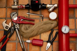 Red collector, close up photography. Thermal sensor. Tow, liquid fum, pipe cutter, scissors for cutting plastic pipes,  adjustable wrench, sanitary wrench.  Close-up photo.