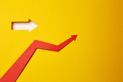Red color arrow cutted from paper made as graph showing growth of stock market or business progress on the yellow background with an arrow shaped hole with white paper underlay showing right direction