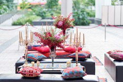 red color design theme with flower vase , table and chair for outdoor corporate event