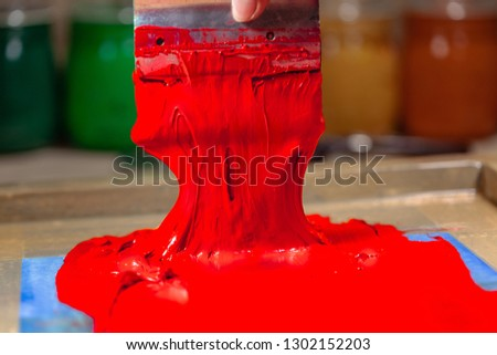 red color dripping from hand screen printing during printing tee shirt in tee shirt factory.