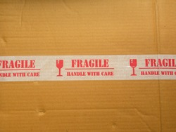 Red color Fragile Handle With Care text on sticker on brown cardboard box