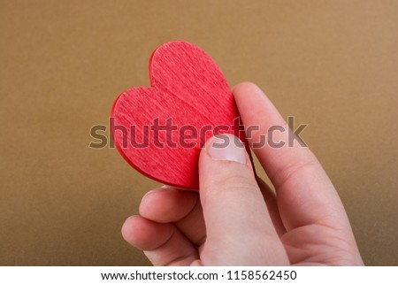 Red color heart shaped object in hand  on dotted paper