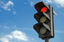 Red color on the traffic light with a beautiful blue sky in background