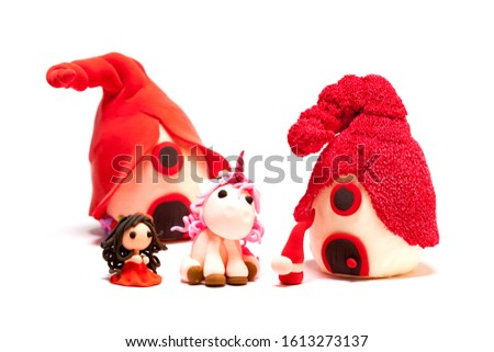 Red color unicorn, gnome, young lady and houses handmade with modelling clay