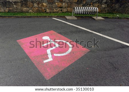 Red colored handicap sign on the parking lot