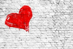 Red colored heart manually painted with drips and dry paint imperfections over a simple grungy white brick wall texture background. Symbolic for love, romance, passion, couple, valentines.