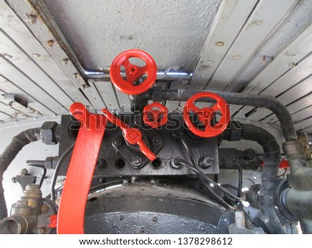 Red colored valves on the old locomotive machine #1378298612