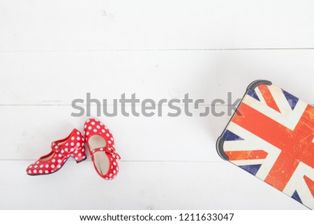 red colorful children's shoes in the peas. Modern stylish trendy trendy multicolor. lie on the white floor next to the flag of Great Britain #1211633047
