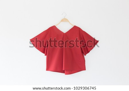 Red colour blouse is clothes hanger on white background.