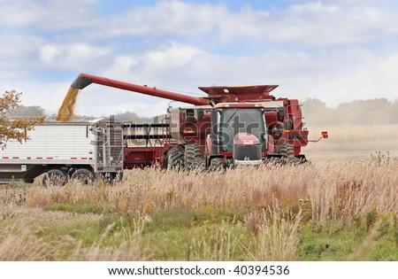 Red combine loading corn into a truck in a farm field