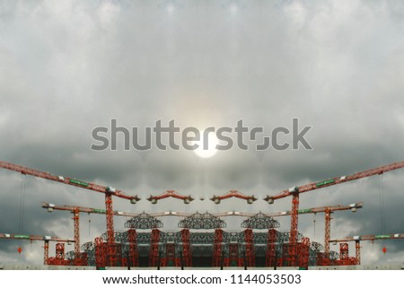 Red construction cranes and building structure over the tower in city with sunset background on a dark and cloudy day. It shows engineering and developed equipment of modern construction in big city.