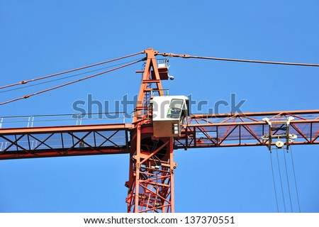 Red construction tower crane against blue sky