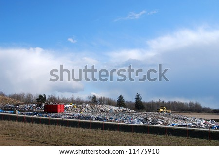 Red container full of waste and bulldozer in the trash dump