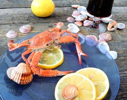 Red cooked crab with sliced fresh lemon on a blue glass plate. Flower crab or blue swimmer crab, or sand crab. Seafood. Edible still life with seashells and glass of wine on old rough wooden surface