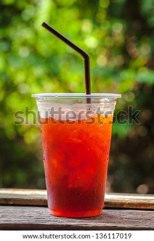 Red cool drink in plastic cup with water bubble against green out focus background