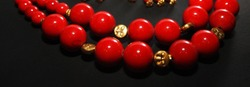 Red coral stone necklace beads decorated with golden beads isolated in dark background