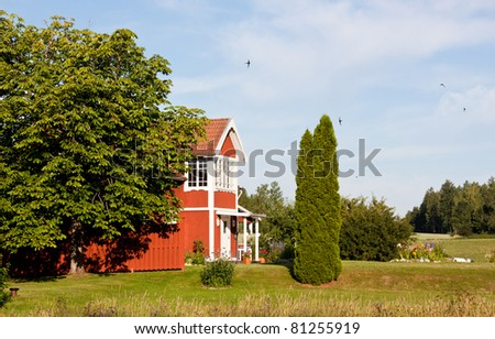 Red cottage in the country in summertime. - stock photo