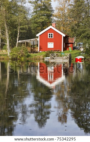 Red cottage with a jetty at the water