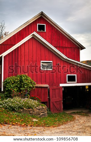 Red country barn with storm clouds in autumn