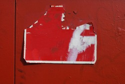 Red cracked damaged street sign with old peeling spray paint