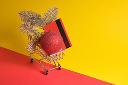 red credit card, fir branch and christmas tree ball in mini shopping trolley on red and yellow background, new year shopping concept