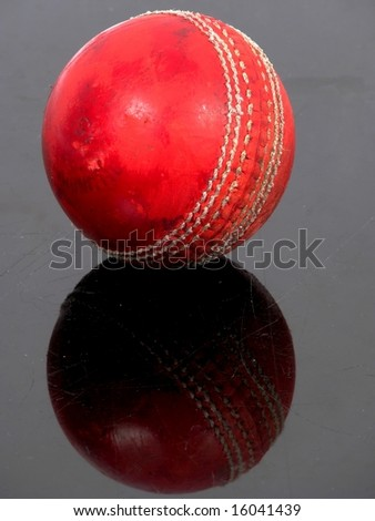 Red cricket ball on a black shiny surface