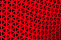 Red crisscrossing pattern blurred abstract light background.