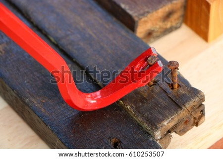Red crowbar pulling a rusty nail to demonstrate the concept of leverage