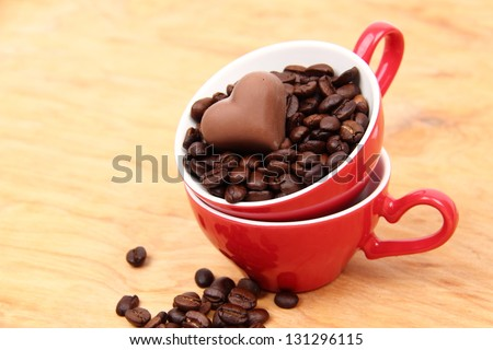 Red cup full of coffee beans and a candy cane from the top on wooden table on Food and Drink