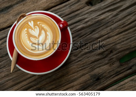 Red cup of cappuccino with beautiful latte art on old wooden background. Top View.