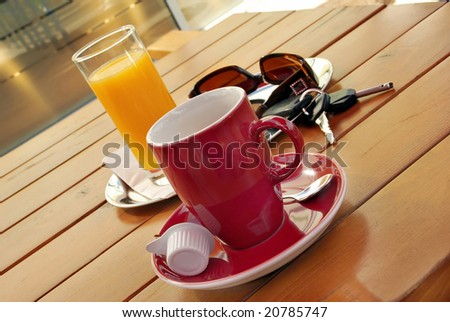 Red cup of coffee, juice, sunglasses and car key on table