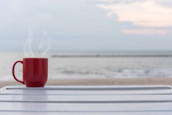 Red cup of coffee on white wood table on sea background at sunrise