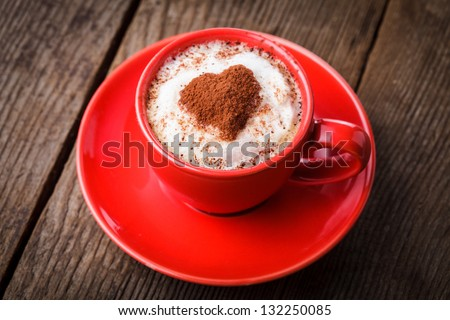 Red cup with cappuccino and heart decoration over foam. Valentine's day cup. Love concept