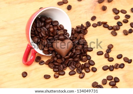 Red cup with coffee beans and sweets in the form of heart on  wooden background on Food and Drink