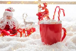 Red cup with hot chocolate marshmallows on white window blanket, christmas composition