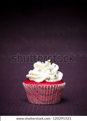 red cupcake with white icing and sprinkles silvery purple abstract background with dots