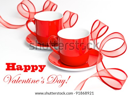 red cups with red ribbon on a white background. valentine's day card concept