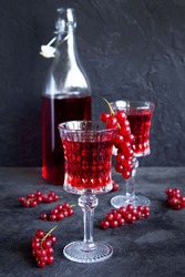 Red currant drinks in a beautiful glass goblets with bottle of  red currant drink on dark grey surface. Bunches of red currants on glasses and on the table